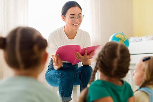 Egy pedagógiai asszisztens gyerekeknek olvas fel